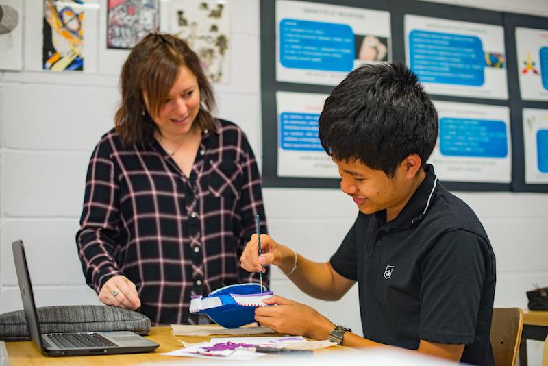 Une enseignante en arts plastiques avec un élève.