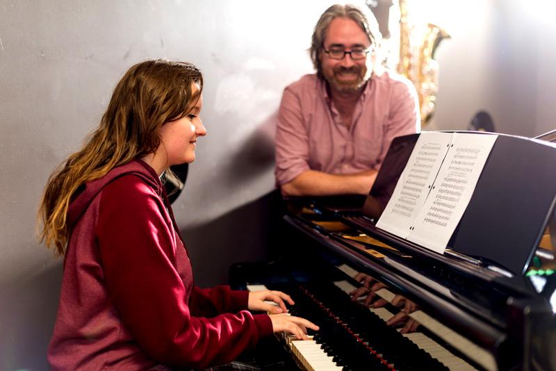 Un professeur supervise une étudiante jouant du piano.